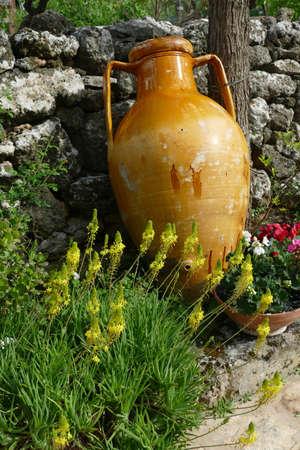 Large ochre amphora urns in garden of Alberobello, Puglia, Italy