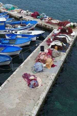 FIshing boats and nets in the marina harbor of Gallipoli, Puglia, Italy