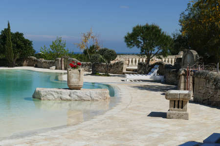 ALBEROBELLO, ITALY - APR 10, 2019 - Outside infinity swimming pool in a luxury villa hotel near Masseria Montenapoleone, near Alberobello, Puglia, Italy 新聞圖片