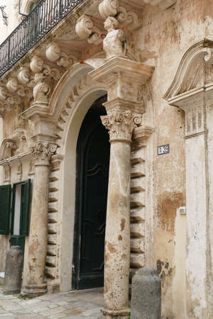 GALLIPOLI, ITALY - APR 7, 2019 - Baroque columns on palace entrance in Gallipoli, Puglia, Italy