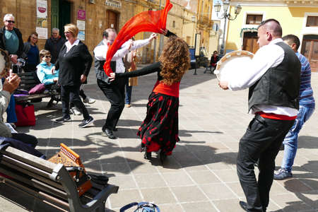 SQUALZINO, ITALY - APR 6, 2019 - Woman in red and men on tambourines playing pizzica music on an accordion, Squalzino, Puglia, Italy 스톡 콘텐츠 - 122236150