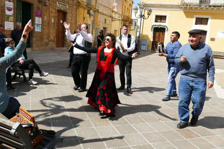 SQUALZINO, ITALY - APR 6, 2019 - Woman in red and men on tambourines playing pizzica music on an accordion, Squalzino, Puglia, Italy