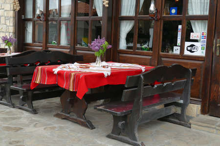 Outdoor restaurant with red tables, Arbanasi, Bulgaria Stock Photo