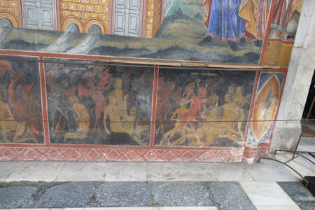 RILA, BULGARIA - APR 13, 2019 - Exterior fresco paintings of sinners condemned to hell, , Rila orthodox monastery, Rila, Bulgaria