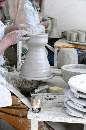 Artist throwing a pot on foot wheel, Artisanal pottery workshop, Fes, Morocco, Africa
