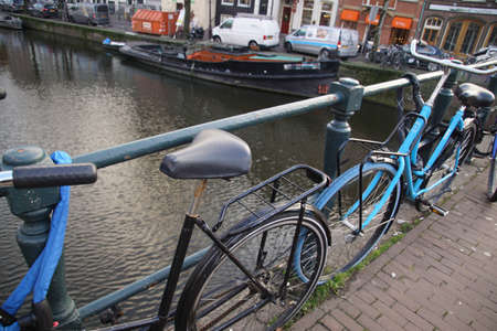 Bicycles on a canal in Amsterdam, Netherlands Sajtókép