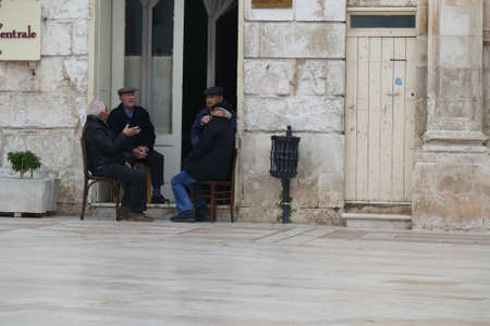 OSTUNI, ITALY - APR 9, 2019 - Old men gather in the piazza in the afternoon, Ostuni, Puglia, Italy