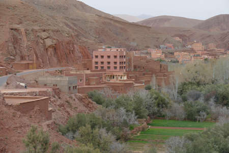 Small village of mud brick houses in the mountain valley near Ouarzazate,  Morocco, Africa Standard-Bild - 124376336