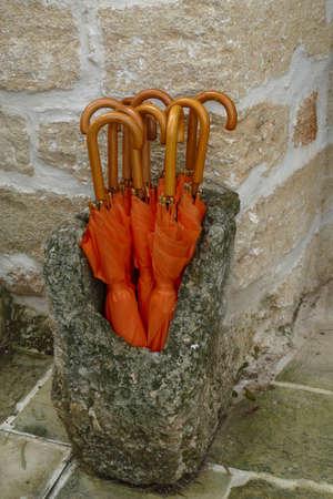 Orange umbrellas in an ancient stone stand, Masseria Trapana, Lecce, Puglia, Italy