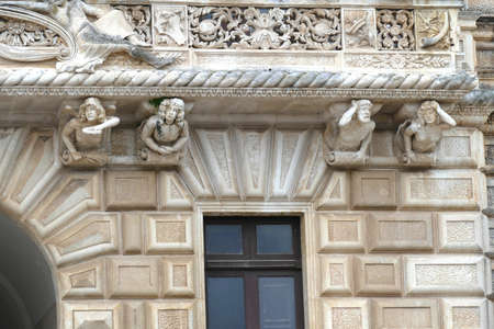 NARDO, ITALY - APR 7, 2019 - Whimsical sculpted figures on struts of a  balcony in Nardo, Puglia, Italy Stock Photo