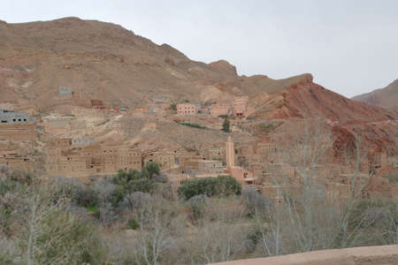 Small village of mud brick houses in the mountain valley near Ouarzazate,  Morocco, Africa Standard-Bild - 124377486