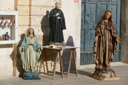LECCE, ITALY - APR 6, 2019 - Small shop selling religious statues on the cathedral square of Lecce, Puglia, Italy
