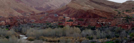 Small village of mud brick houses in the mountain valley near Ouarzazate,  Morocco, Africa Standard-Bild - 125125725