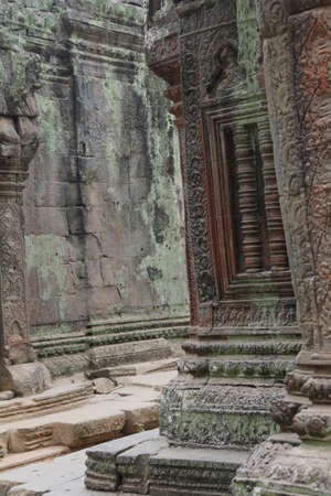 Ancient temple with carvings recovered from the jungle in Ta Prohm,  Siem Reap, Cambodia