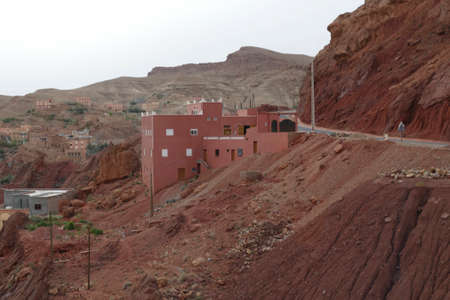 Small village of mud brick houses in the mountain valley near Ouarzazate,  Morocco, Africa Standard-Bild - 125127190