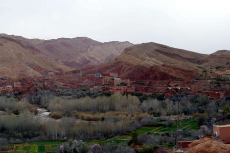 Small village of mud brick houses in the mountain valley near Ouarzazate,  Morocco, Africa Standard-Bild - 125127333