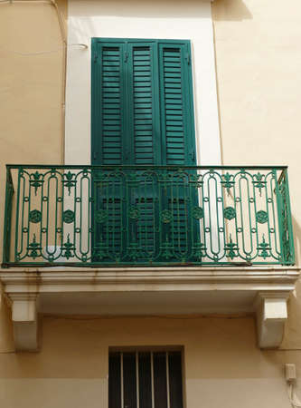 Green door and balcony of a baroque palace in Gallipoli, Puglia, Italy