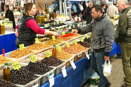 CANAKKALE, TURKEY - APR 21, 2019 - Buying olives in the central market of Canakkale, Turkey