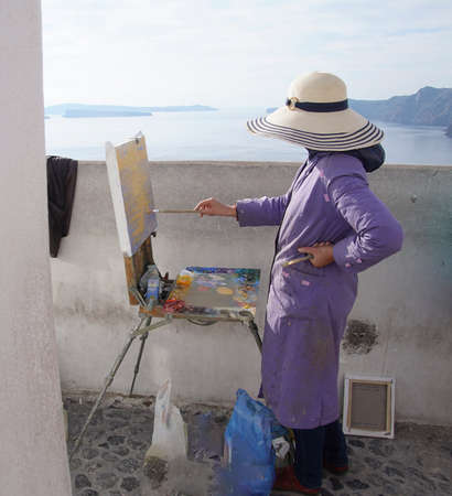 Woman painting  with oils in Santorini, Greece Фото со стока