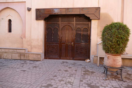 Beautiful carved wooden doors of a home in the medina bazaar of Marrakech,  Morocco, Africa 免版税图像