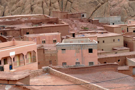 Small village of mud brick houses in the mountain valley near Ouarzazate,  Morocco, Africa Standard-Bild - 127501561