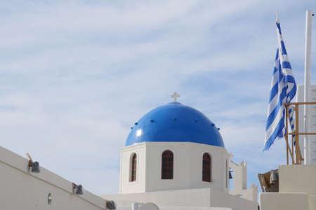Blue domed building and Greek flag in Santorini, Greece