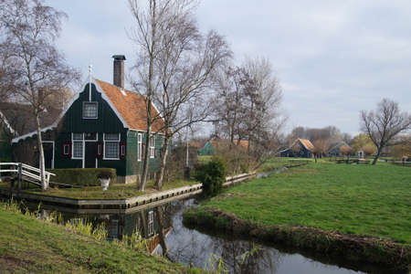 Traditional Dutch home on canal in Zaanse Schans, Netherlands Фото со стока