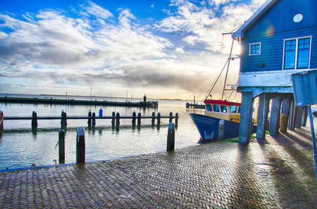 Fishing boats moored in the marina and waterfront of Volendam, Netherlands Фото со стока