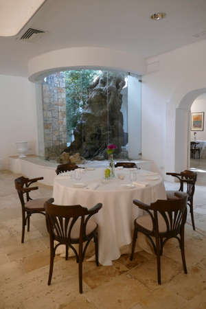 BRINDISI, ITALY - APR 11 2019 - Dining room and lounge built around ancient olive trees at a masseria near Brindisi, Puglia, Italy Standard-Bild - 129119877