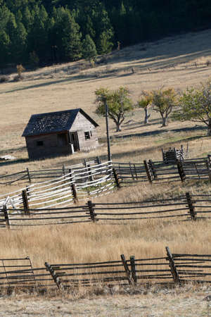 Old wooden barn leaning on hillside with autumn fileds and fences in eastern Washington