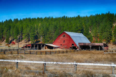 Old red wooden barn  with autumn fields and fences in eastern Washington
