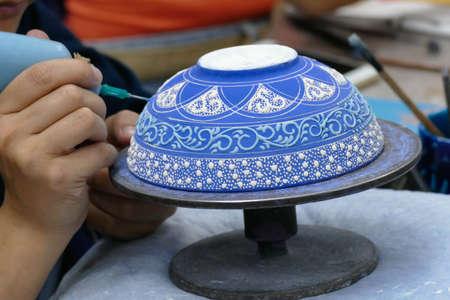 CAPPADOCIA, TURKEY - SEP 11, 2019 - Artist paints unfired pottery in a factory in Avanos, Turkey