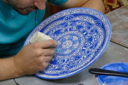 CAPPADOCIA, TURKEY - SEP 11, 2019 - Artist paints unfired pottery in a factory in Avanos, Turkey Editorial