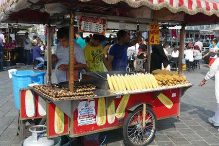 ISTANBUL, TURKEY - SEP 5, 2019 -  A street vendor sells roasted chesnuts and corn near the Galata Bridge in Istanbul,  Turkey