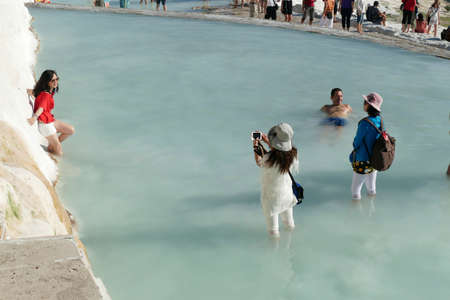 PAMUKKALE, TURKEY - SEP 17, 2019 -  Tourist photograph each other in the travertine turquoise  terraced pools at  Pamukkale,  Turkey