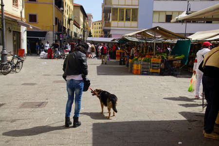 LIVORNO, ITALY - APR 23, 2018 - Woman and her dog in the market of Livorno, Italy