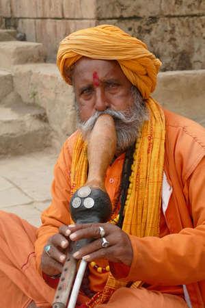 VARANASI, INDIA - DEC 24 2019 - Snake charmer with his snakes on the ghats of Varanasi, India 新聞圖片