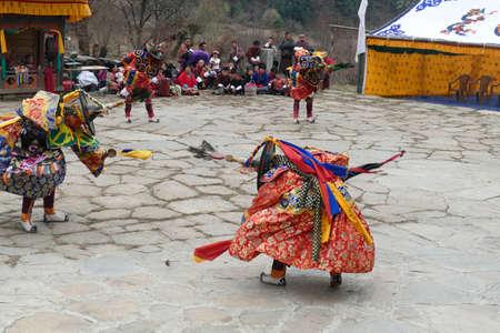 BUMTHANG, BHUTAN - DEC 13, 2019 - Red skirt Black hat dancers Zhang cham   celebrate victory of good over evil,    Nalakar Tsechu Dance Festival , Ngala Lhakhang Temple Bumthang,  Bhutan 新聞圖片