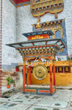 BUMTHANG, BHUTAN - DEC 14, 2019 - Large gong and prayer wheels outside Kenchosum Lhakhang temple of the Three Jewels, Bumthang,  Bhutan Redakční