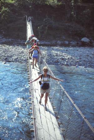 LANGTANG, NEPAL - OCT 15, 1986 - Trekkers cross a rickety suspension bridge over a river in Helambu, Nepal