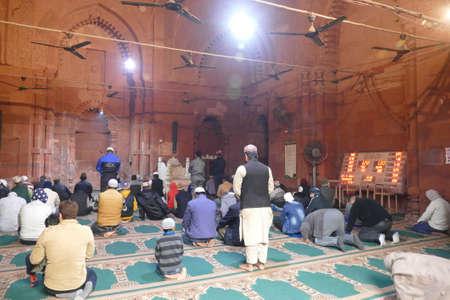 DELHI - DEC 19, 2019 - Muslim men gather at their mosque for noon prayers in the Nizamuddin area of Delhi, India
