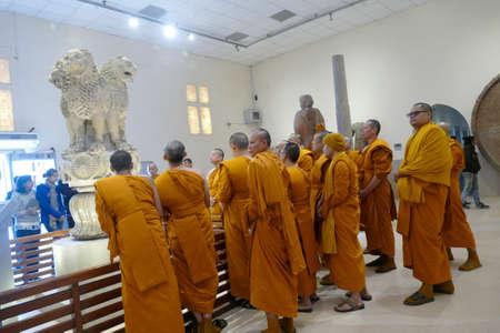 SARNATH, INDIA - DEC 23, 2019 - Buddhist monks examine sculptures in the museum at Sarnath near Varanasi, India