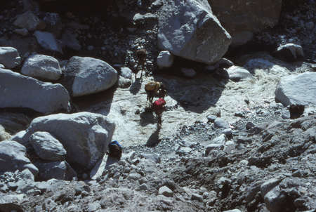 ARUN VALLEY, NEPAL - OCT 17, 1987 - Porters carrying loads across river,Arun Valley,  Himalyas, Asia 報道画像