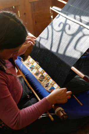 THIMPHU, BHUTAN - DEC 10 2019 - Young woman working a backstrap loom in Thimphu, Bhutan 報道画像
