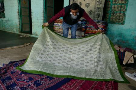 JODHPUR, INDIA - JAN 4, 2020 -  Local weaver displays dhurries,    thin flat-woven rug or carpet used traditionally in South Asia as floor-coverings, Jodhpur, Rajasthan, India