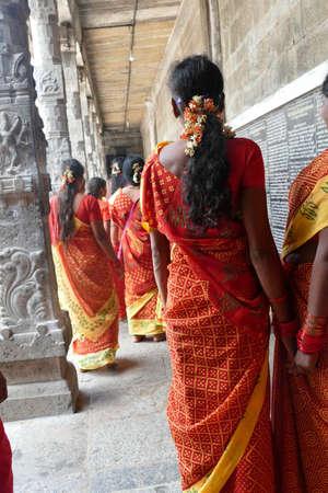 KANCHIPURAM, INDIA - DEC 26, 2019 - Women pilgrims wear red sarees in the Maha Mandapa meeting hall of the Ekambareshwara Temple, 16th - 17th century, Kanchipuram, Tamil Nadu , India Sajtókép