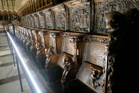 TOLEDO, SPAIN - MAR 2, 2020 - Carved mahogany choir seats in Cathedral of Toledo, Spain