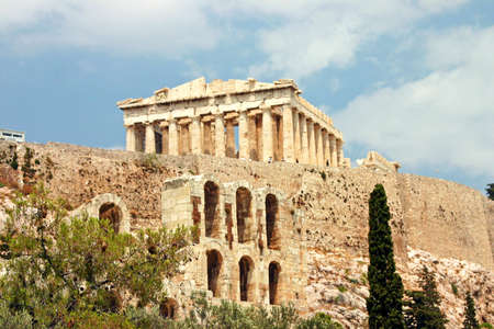 View of the Parthenon atop the Mighty Acropolis.  Foreground Temple of Herod Atticus Athens, Greece Фото со стока