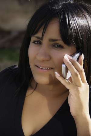 Hispanic Woman in Black talking on a Cell Phone Фото со стока
