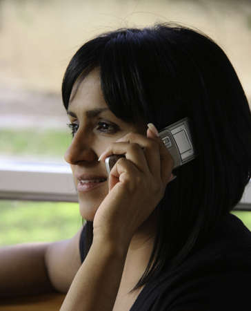 Hispanic Woman Sitting and talking on a Cell Phone